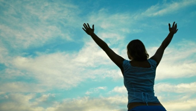 Young girl raising her arms to sky